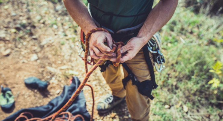 man tying rope around his waist for rock climbing