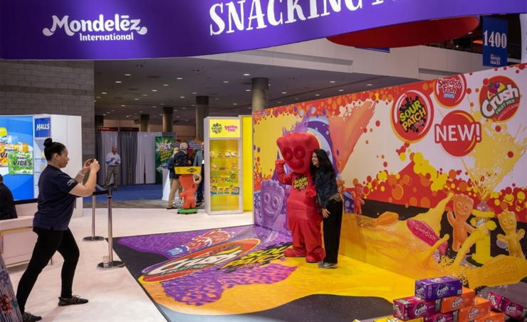 Woman demonstrating touch screen in Mondelez booth by Derse